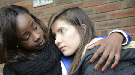 A young woman suffering from depression is consoled by her friend.