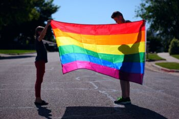 Two people holding a multi coloured rainbow flag
