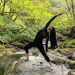 Yogo Claire doing yoga standing in a stream in a forest.