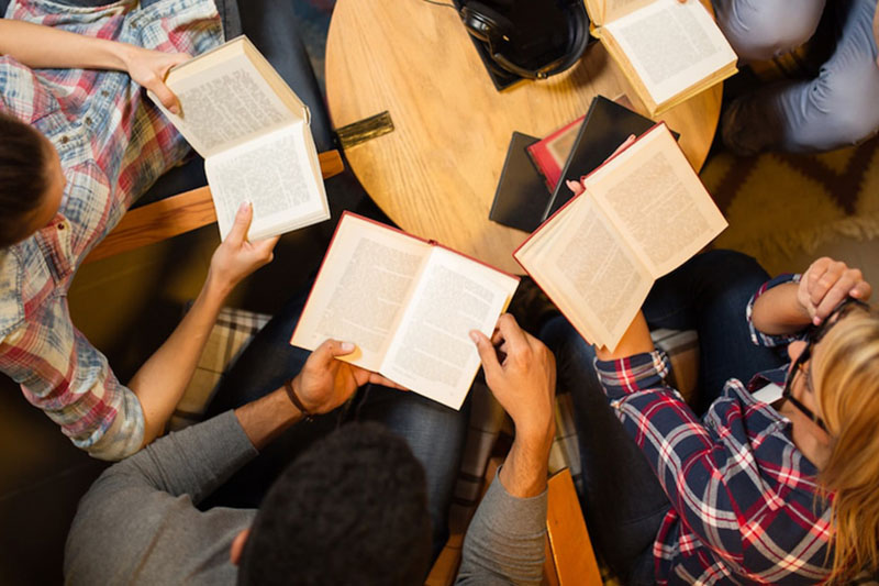 People in a reading group sitting around a table holding books